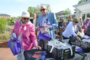 High Point community members collect free reusable grocery bags and dahlia flower bulbs after the ceremony.