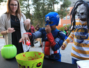 "Sophomore Caroline Davis looks on as Captain America plays the ""ducks in guts"" game at the trick-or-treat party."