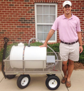 Holder stands next to one of the water-tank carts he made on his back porch in Clayton