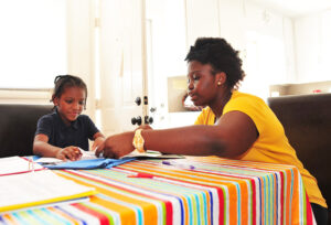 Junior Briayna Cuffie offers homework help to a 6-year-old student.