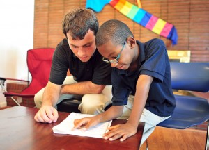 An HPU student volunteer gives homework help at the Community Writing Center.