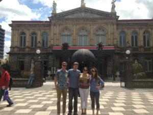 Jordan, adjunct professor of piano Jacob Hahn, Daneman and Siebeneichen stand in front of the National Theatre of Costa Rica.