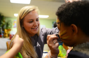 Junior Lexi Valentinas paints tiger whiskers on a student's face.