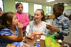 Freshman Whitney Bosserman helps children sort through the Easter egg candy they found.