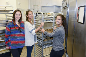 HPU students Jessie Massey (left), Andrea Tishman and Gabby Vigorito prepare to move food to Open Door Ministries.