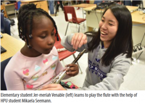 Elementary student Jer-meriah Venable (left) learns to play the flute with the help of HPU student Mikaela Seemann.