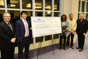 Holder (second from left) receives a check for $500 and is honored as the first place winner of the Elevator Pitch Competition by judges (from left to right) Gary Simon, president of Simon Jewelers; Bridget Chisholm, managing partner at BWC Consulting; Eric Hill, chief operating officer and co-founder of BioRX; and Mark Phillips, CEO and president of the Phillips Collection.
