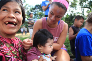 Caitlin Kane puts a beaded necklace on one of the babies in a Guatemalan village.