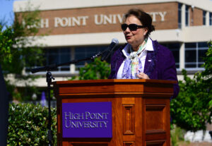 The photo features HPU First Lady Mariana Qubein, who has spearheaded the arboretum and gardens on campus, speaking at the Arbor Day celebration.