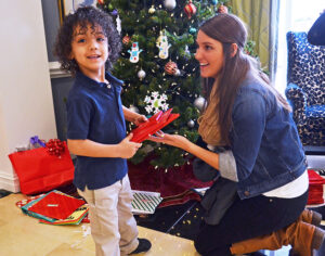 HPU junior Amy Jamil helps Rodyrick, her Montlieu Academy book buddy, find his gifts under the Festival Tree.