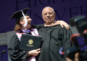 Powell shakes the hand of HPU graduate Eugenia Copeland as she crosses the stage to receive her degree.