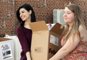 "Students Ninaru Shtayyeh (left) and Bridget Hess (right) participate in the ""Feed Their Legacy"" food drive for the Out of the Garden Project."