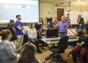 Children from the Salvation Army Boys and Girls Club gather with their families and HPU students in the design lab in the Nido Qubein School of Communication to reveal the video game characters they've created.