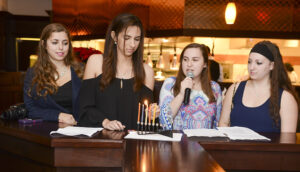 From left to right, HPU students Lindsay Katz, Sam Berg, Jordan Kenter and Fronstin read the story of Hanukkah at the Hanukkah dinner on HPU's campus.