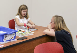 HPU student Courtney Clayton (right) works with community member Abby Tarara (left) on a Lego project.