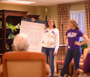 HPU students Ally Kane (left) and Jessie Drew lead one of many poetry writing sessions with residents at Pennybyrn at Maryfield in High Point through the HPU Lifelines program.