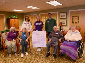 The students and senior citizens display one of their completed poems.