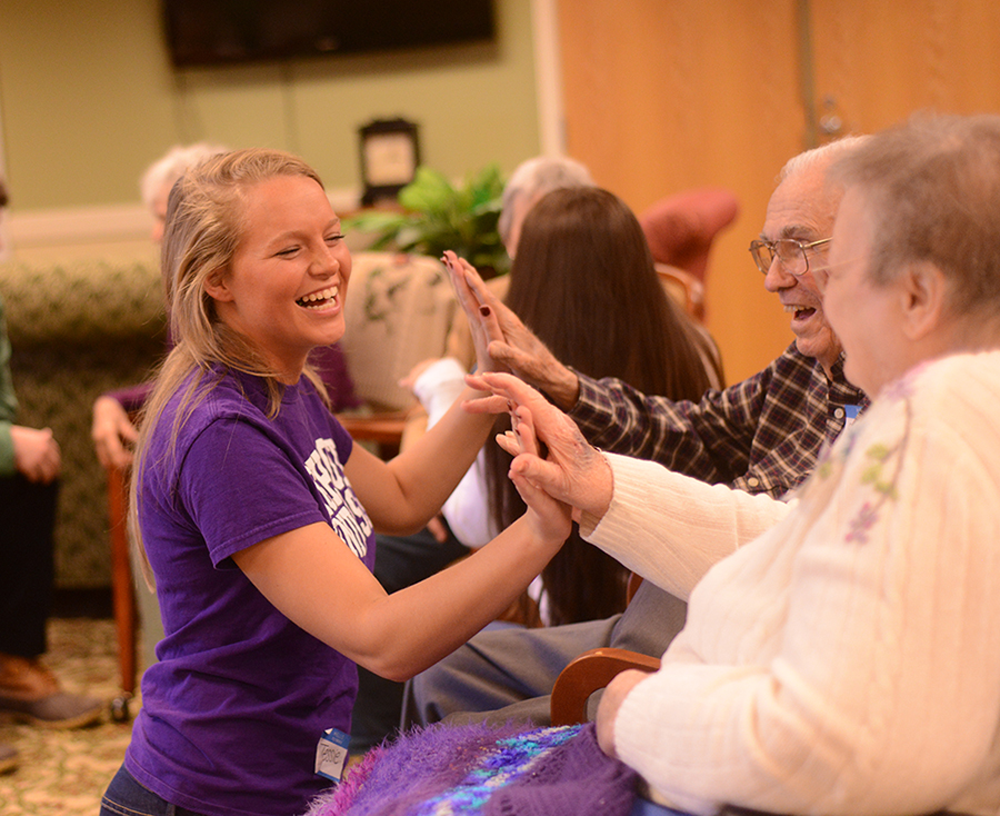 Jessie Drew shares congratulatory handshakes and high fives with the senior citizens for the completion of two poems in the session.