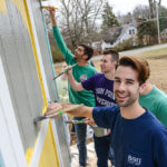 Members of HPU's Beta Theta Pi fraternity paint a shed at the Howard Street Community Garden.