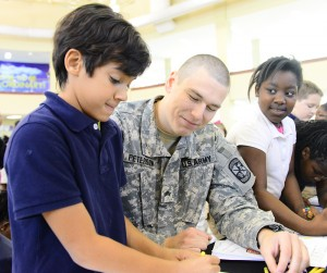 ROTC member Chris Peterson, center, helps Montlieu student Sebastian Mata, left, decorate a thank-you card to send to U.S. troops overseas.