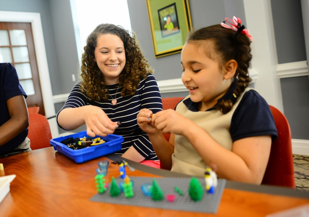 Education major Callie Moore helps a second-grader from Montlieu Academy of Technology build a lake habitat with LEGOs to learn about the life cycle of a fish.