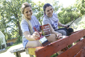 HPU students Morgan Hicks and Nikki Mehan paint a bench at Bountiful Harvest Community Garden.