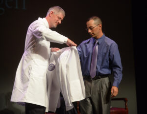 Dr. Stephen Meyers, medical director of the Department of Physician Studies at HPU, presents student Shane Georgeff with his white coat.