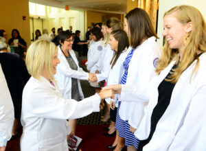 Ashlyn Bruning, director of clinical education at HPU, congratulates student Lindsay Webster on receiving her white coat.