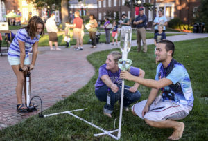 Maddie Brown (left) launches a water bottle rocket during High Point University's 2015 HPUniverse Day with HPU student Carrie Wilson (center) and HPU student Nick Casle (right).