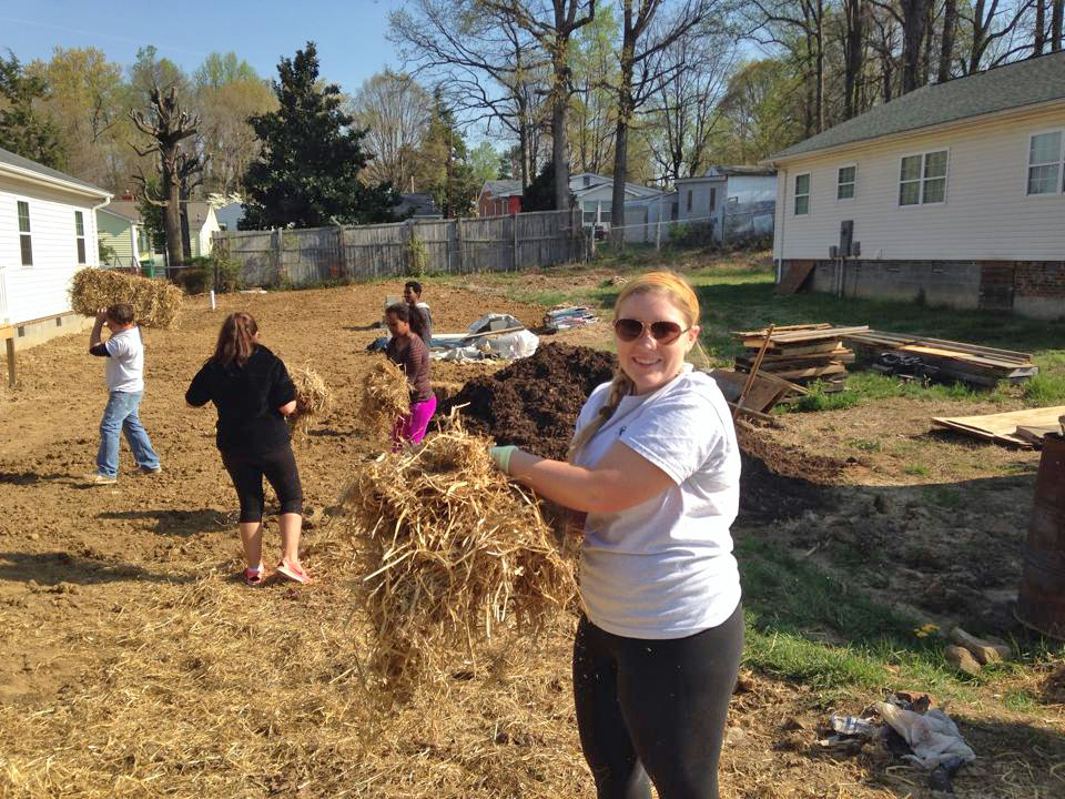 HPU Habitat for Humanity chapter president Taylor Hemphill lays straw on the lawn of a build site during Act! Speak! Build! Week.