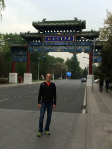 Eric Hegedus stands outside the main gate to the Beijing Sports University.