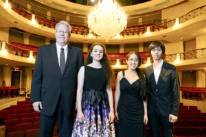 The photo features (from left to right) piano competition judge Steven Heyman, first place winner Aleksandra Kasman, second place winner Priscila Navarro and third place winner Tianpeng Yu.