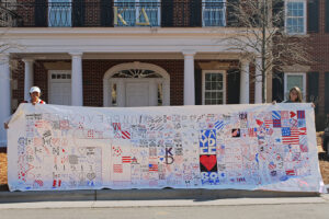 Kappa Delta sisters Kelly Clark and Alyssa McFarland hold up the sorority's prayer canvas, which was created in remembrance of the 2013 Boston Marathon tragedy.