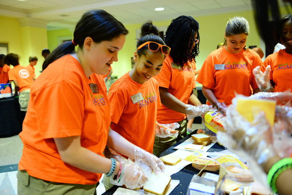 Local teens who participated in the HPPD/HPU Leadership Academy make lunches for the High Point Housing Authority.