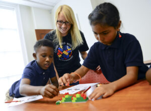 First-grade student Elias Page, HPU graduate student Ali Smiley and first-grade student Miracle Harley build with Legos during a MoreToMath activity.
