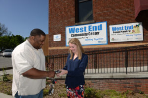 The photo features Chris Gillespie, executive director of West End Ministries, and Megan Muir, HPU student, with the old and new lock and key system for West End Ministries.