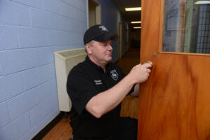 The photo features Chip Southern, HPU security officer, installing the new lock and key system.