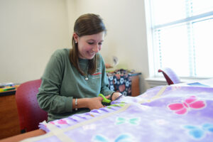 Jordan Herring cuts strips to tie her blanket's fabrics together.