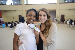 A Montlieu student and HPU sophomore Caroline Davis show off a butterfly craft made with coffee filters and pipe cleaners.