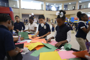 Children write thank-you letters to loved ones, donning their butterfly bows and bow-ties.