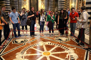 Students view the 'Ruota della Fortuna' (Wheel of Fortune) which was laid in 1372 and restored in 1864.