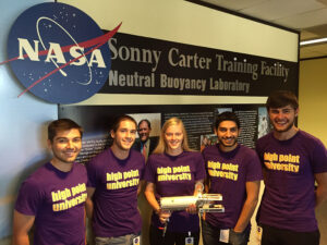 "High Point University students (left to right) Matthew Iczkowski, Jacob Brooks, Hallie Stidham, Simeon Simeonides and Michael Cantor at the NASA Johnson Space Center in Houston with their handheld apparatus, the ""Chip n Ship,"" that NASA tested."