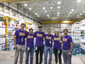 The photo features (left to right) Dr. Brad Barlow, assistant professor of astrophysics, Simeon Simeonides, Michael Cantor, Jacob Brooks, Hallie Stidham and Matthew Iczkowski at the Johnson Space Center NBL.