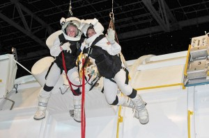 Harnessed students Ketchem and Byrd repair a spacecraft during an external vehicular activity to simulate the challenges of limited mobility, gravity and the intense heat that astronauts face when in space.