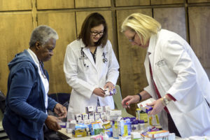 Dr. Robin Cooke (right), assistant professor of ambulatory care at HPU, and Dr. Christina Sherrill (center), assistant professor of clinical sciences at HPU, give community members free over-the-counter medication.