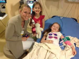 Page provides Madelyn, 6 with supplies to decorate her IV preparation doll.