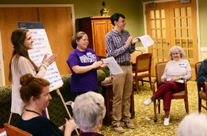 The photo features from left to right HPU students Jessica Mackintosh, Megan Jordan, Dalton Sheppard and Pennybryn resident Liz Aversa writing a poem.