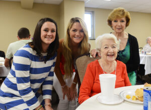 The photo features (from left to right) HPU student Kate Aitkens, HPU student Lexi Deignen, Pennybryn resident Delphine Ebert and Sarah Shelton, activities director at Pennybryn, at the poetry celebration lunch.