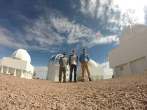From the left, Vasquez, Filik and Dr. Brad Barlow, assistant professor of astrophysics, are pictured with the SMARTS telescope and 4-m Blanco telescope in Chile.
