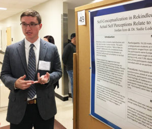 """Senior Jordan Izzo, a psychology major, presents his research poster, """"Self-Conceptualization in Rekindled Relationships: How One's Ideal and Actual Self Perceptions Relate to On-Again/Off-Again Relationships."""""""